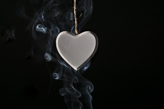 white heart hanging in front of black background with smoke curling around it