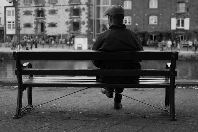 waiting man sitting on bench by street