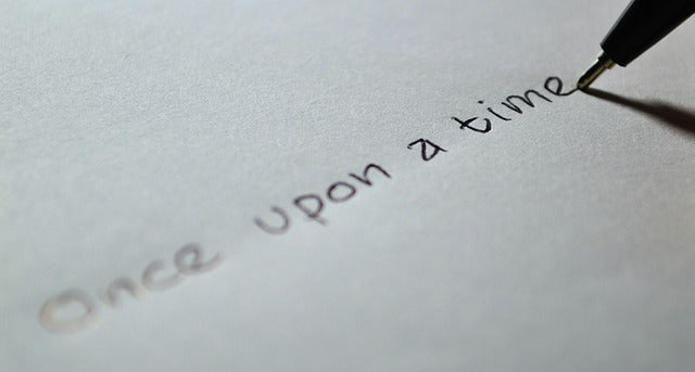 """""""one upon a time"""" being written on paper by a pen"""
