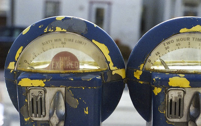 "two parking meters with one showing ""time expired"""