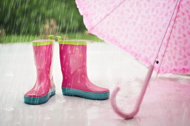 pink boots and umbrella on sidewalk in the rain