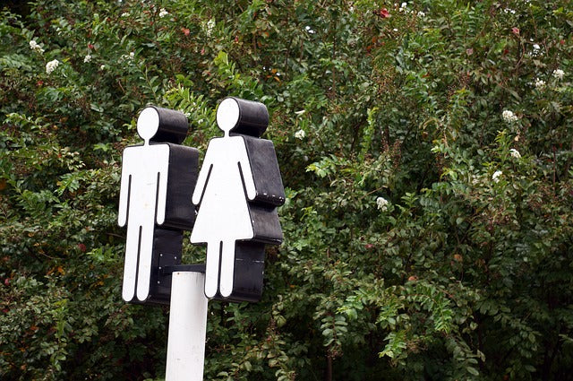 white figures of man and woman on sign against background of trees