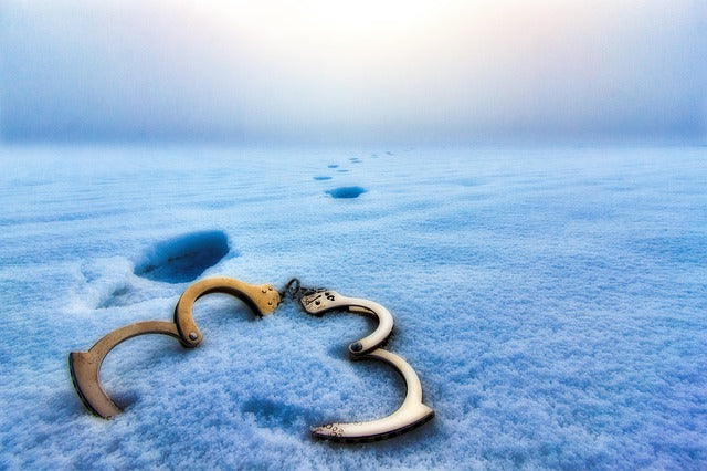 open shackles in snow with footsteps walking away