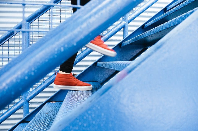 a person's feet in orange shoes climbing a blue staircase