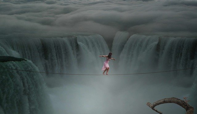 woman walking on tightrope over spray of large waterfalls