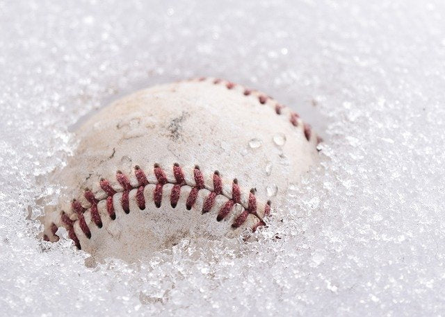 baseball poking through surface of melting snow
