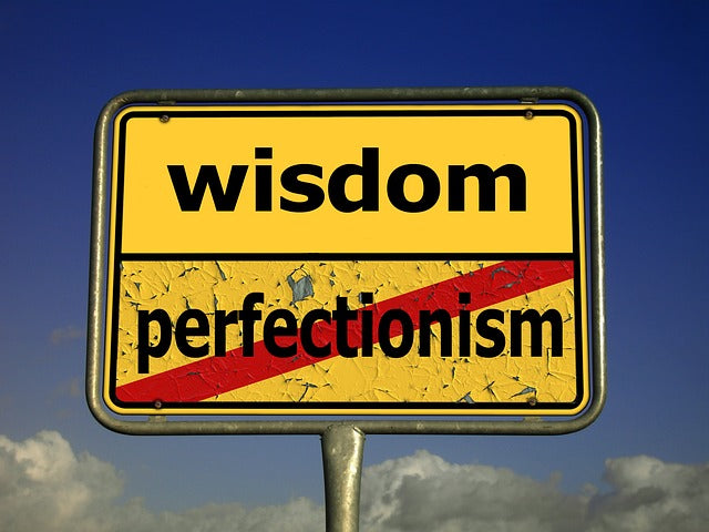 Sign with the word wisdom and a red line through the word perfectionism