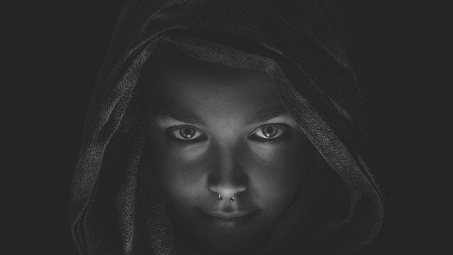 face of girl in the darkness wearing a hood
