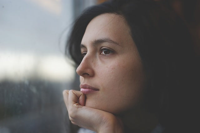 woman with chin on hand pensively staring out a window