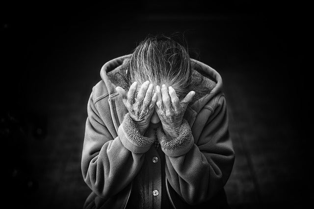 elderly woman with her hands covering her face in black and white against black background