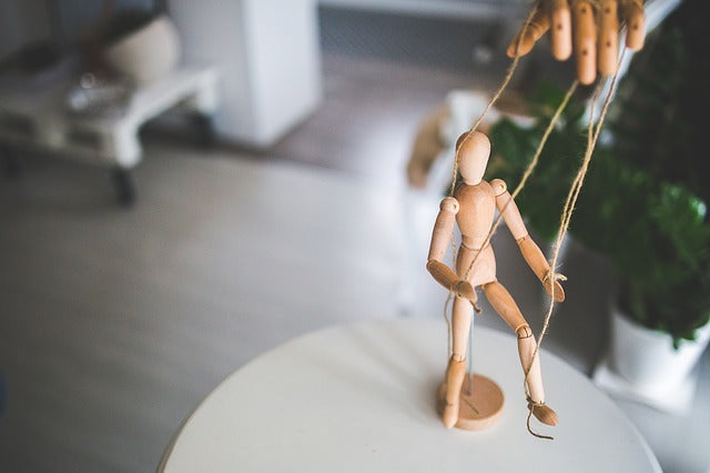 a wooden marionette on a table being controlled by strings