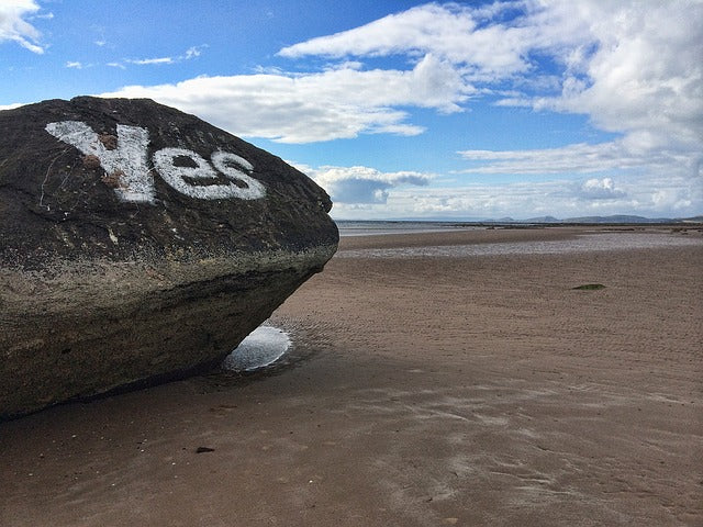 large rock on sandy beach with work YES written on it