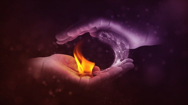 Yin yang symbol formed with two hands - one containing fire and one containing ice