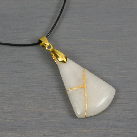 White stone pendant with kintsugi repair on black cotton cord from A Kintsugi Life