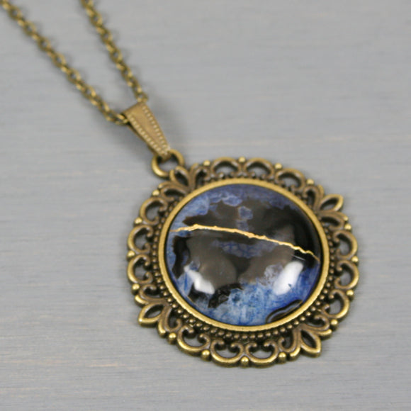 Black and blue druzy agate kintsugi pendant in antiqued brass setting on chain