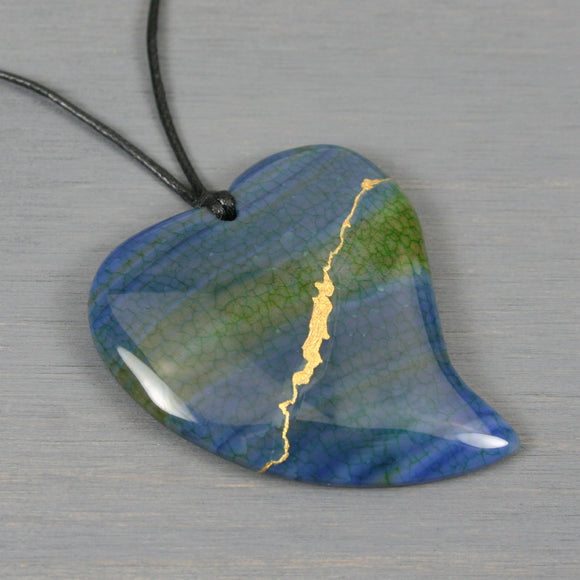 Blue and green agate broken heart pendant with kintsugi repair on black cotton cord