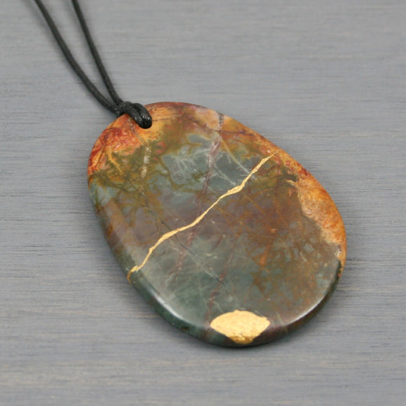Dark red cherry creek jasper pendant with kintsugi repair on black cotton cord