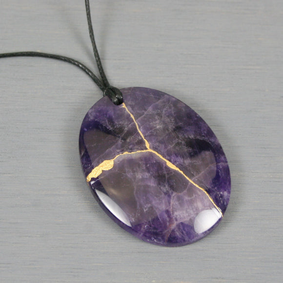 Amethyst pendant with kintsugi repair on black cotton cord