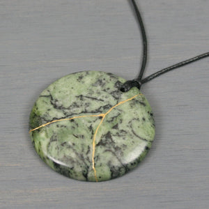 Green crazy lace agate pendant with kintsugi repair on black cotton cord