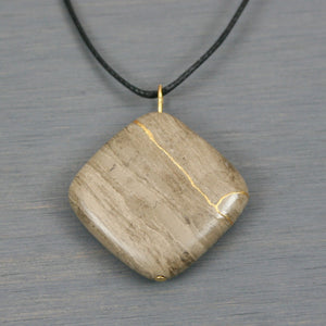 Grey cream marble pendant with kintsugi repair on black cotton cord