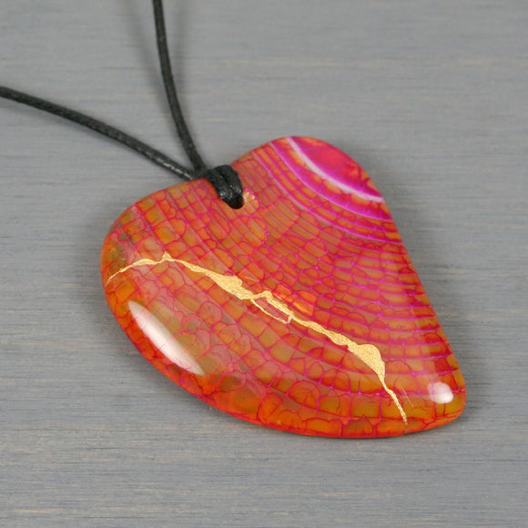 Pink-orange dragon veins agate broken heart pendant with kintsugi repair on black cotton cord