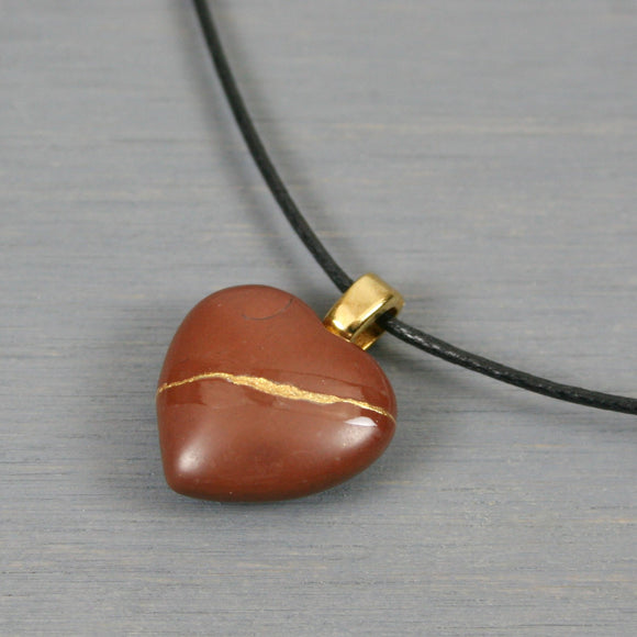 Reddish brown stone broken heart pendant with kintsugi repair on black cotton cord