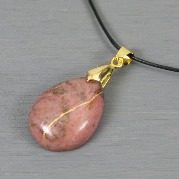 Rhodonite pendant with kintsugi repair on black cotton cord