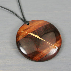 Red tiger eye pendant with kintsugi repair on black cotton cord