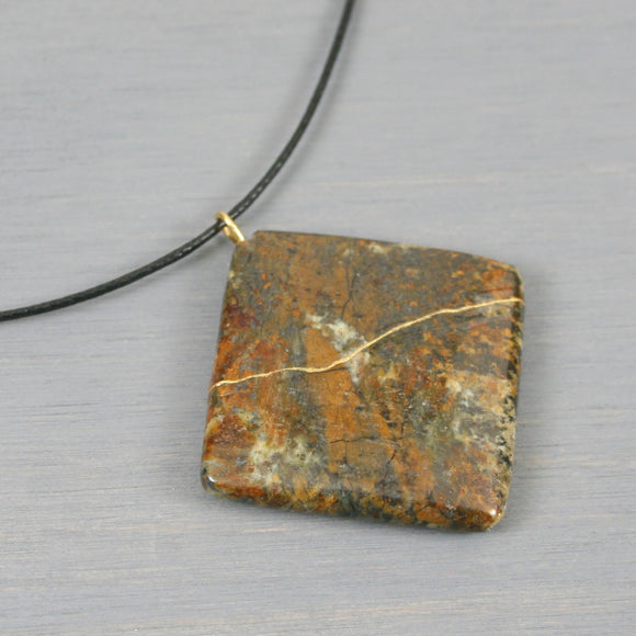 Frement jasper pendant with kintsugi repair on black cotton cord