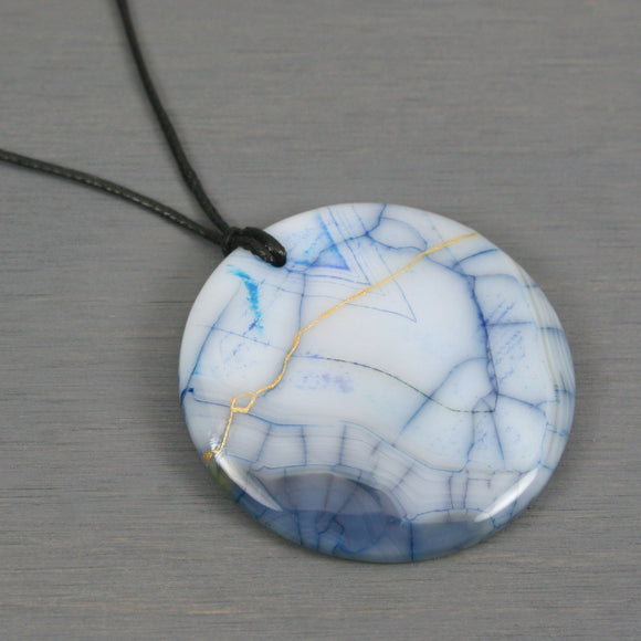 White and blue dragon veins agate pendant with kintsugi repair on black cotton cord
