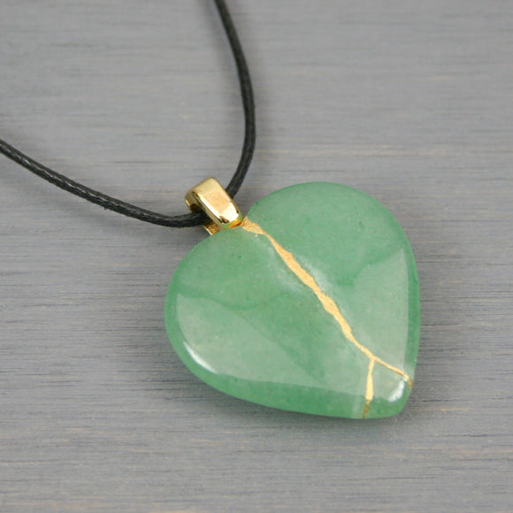 Green aventurine broken heart pendant with kintsugi repair on black cotton cord