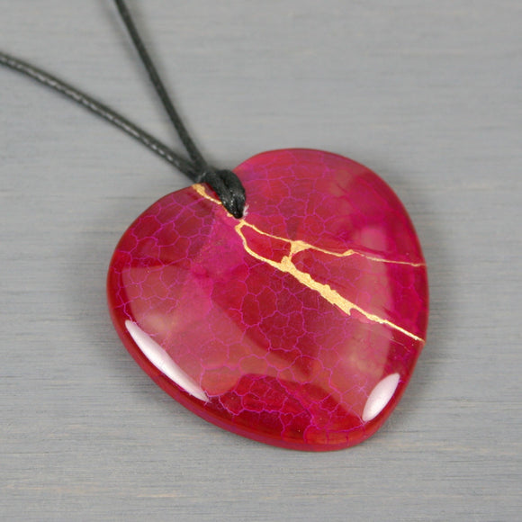 Dark pink agate broken heart pendant with kintsugi repair on black cotton cord