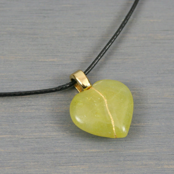 Green stone broken heart pendant with kintsugi repair on black cotton cord