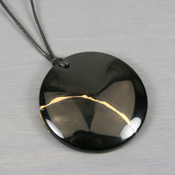 Black onyx pendant with kintsugi repair on adjustable length black cotton cord