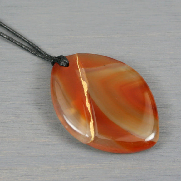 Red agate pendant with kintsugi repair on black cotton cord