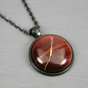 Red tiger eye kintsugi pendant in black setting on chain