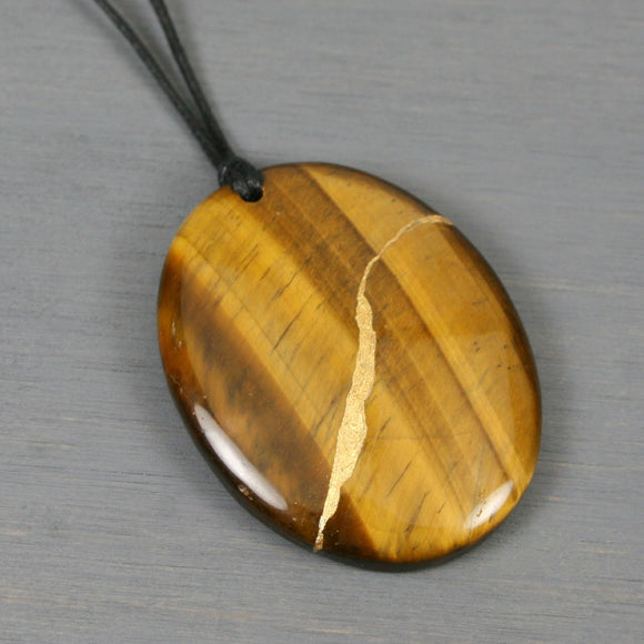 Tiger eye pendant with kintsugi repair on black cotton cord