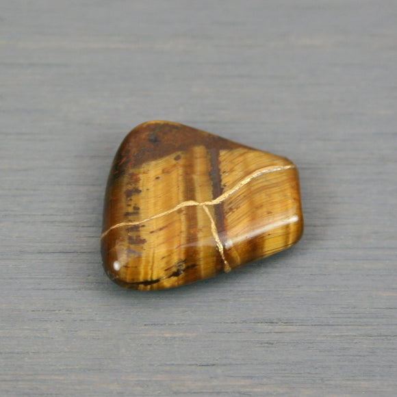Small kintsugi repaired tiger eye tumbled stone