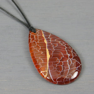 Red dragon veins agate teardrop pendant with kintsugi repair on black cotton cord