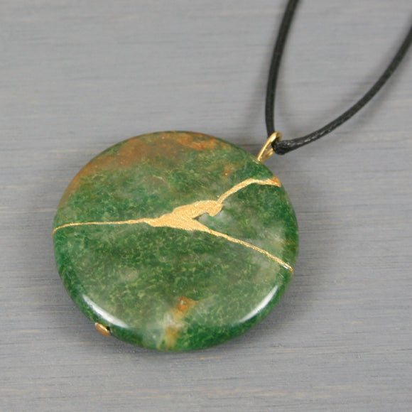 African jade round pendant with kintsugi repair on black cotton cord
