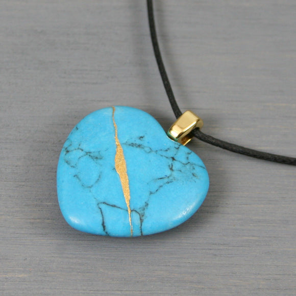 Turquoise magnesite broken heart pendant with kintsugi repair on black cotton cord