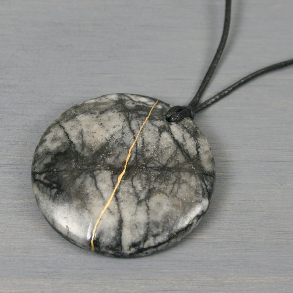 Black and grey marble pendant with kintsugi repair on black cotton cord