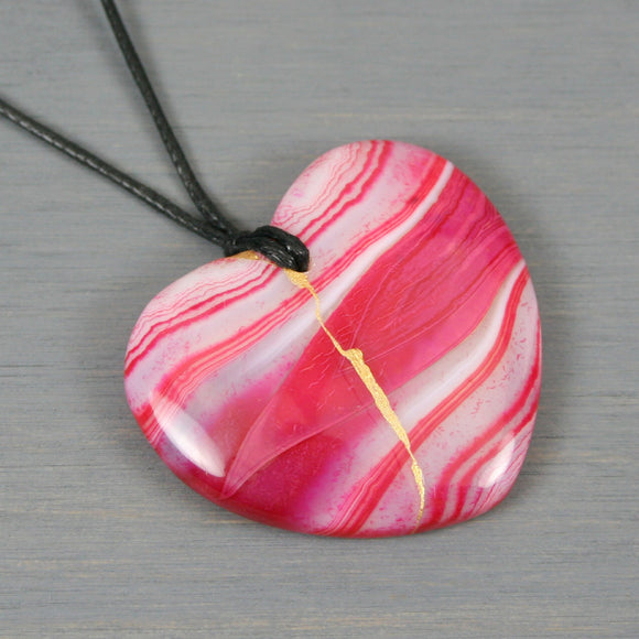 Pink striped agate broken heart pendant with kintsugi repair on black cotton cord