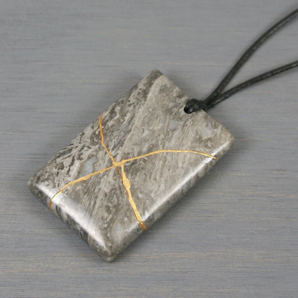Black lace marble pendant with kintsugi repair on black cotton cord