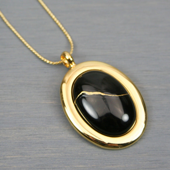 Black onyx kintsugi pendant in a gold setting on chain