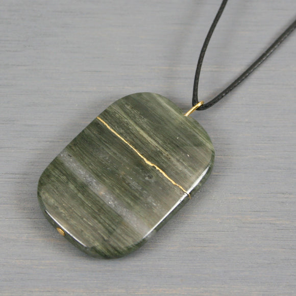 Green seaweed quartz pendant with kintsugi repair on black cotton cord