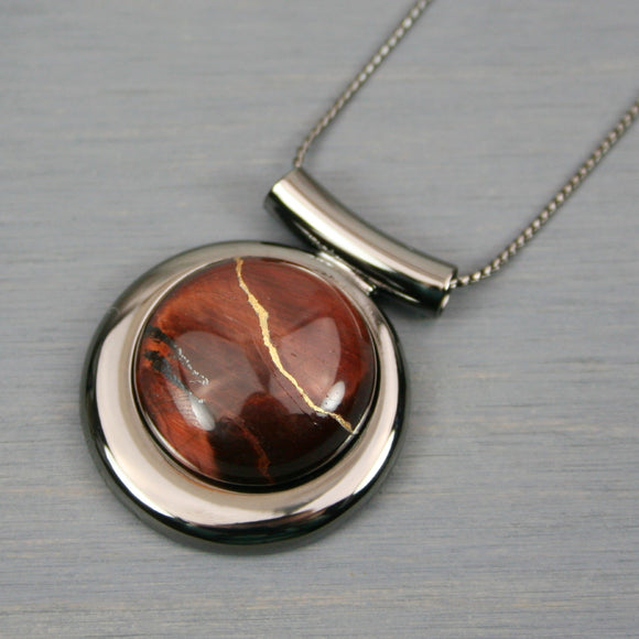Red tiger eye kintsugi pendant in a gunmetal setting on chain