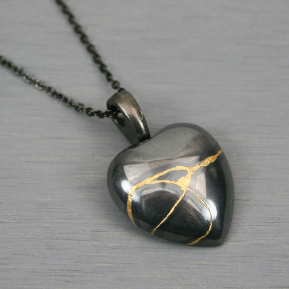 Hematite broken heart pendant with kintsugi repair on chain necklace