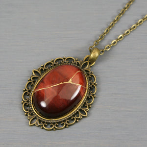 Red tiger eye stone kintsugi pendant in an antiqued brass setting on chain