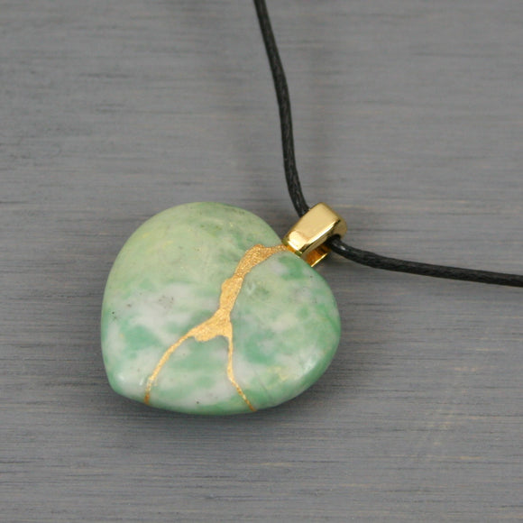 Green and white stone broken heart pendant with kintsugi repair on black cotton cord